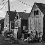 Black and white image of wooden fishing shacks in Rockport, MA.
